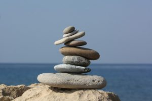 Stack of flat rocks, balanced but tilted.